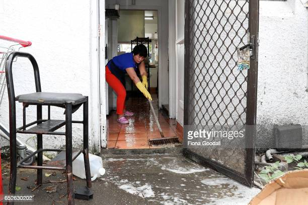Hui Qui cleans up her takeaway shop after flash flooding in Great North Rd New Lynn on March 13 2017 in Auckland New Zealand The Tasman tempest...