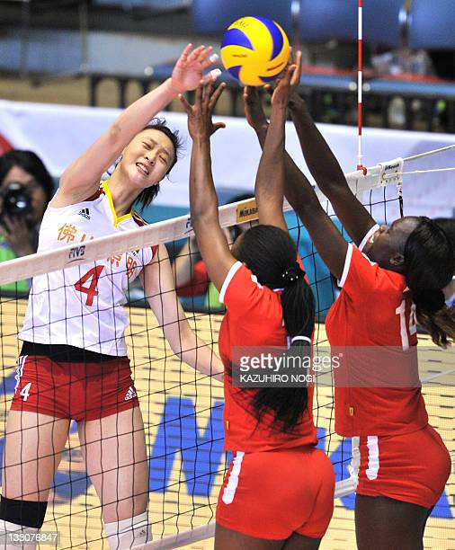 Hui Ruoqi of China attacks over Kenyan players Diana Khisa and Mercy Moim during a match of the World Cup women's volleyball tournament in Tokyo on...