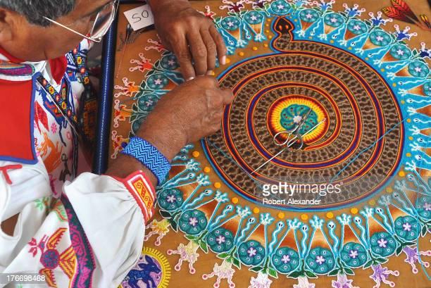 Huichol Indian yarn painter Mariano Navarro from Mexico demonstrates his art at the International Folk Art Market in Santa Fe New Mexico The Huichol...