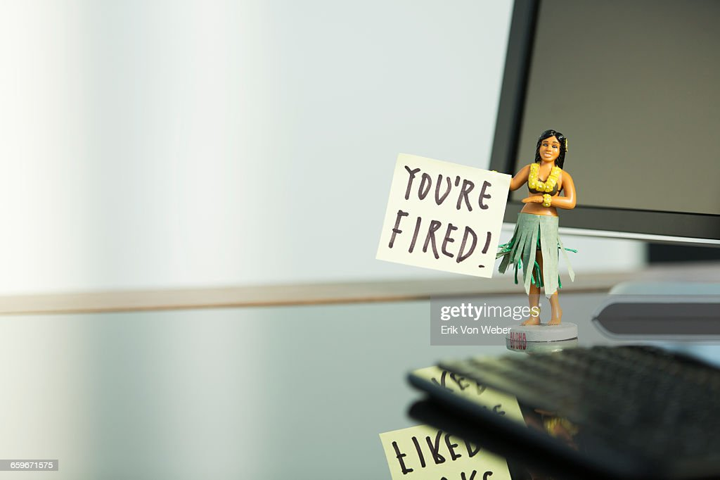 hula girl figurine with post it note on desk : Stock Photo