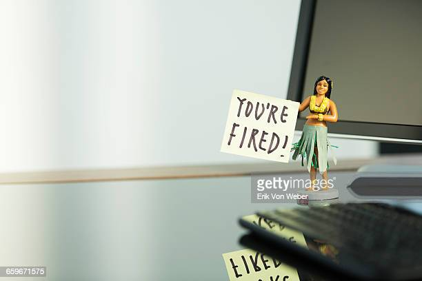 hula girl figurine with post it note on desk