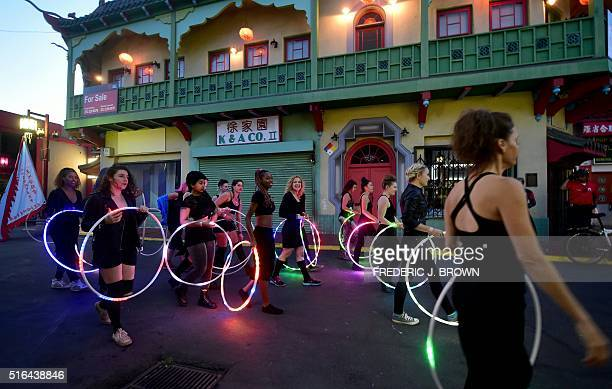 Hula Hoop enthusiasts arrive for a flash mob with their LEDlit hoops in Chinatown Los Angeles on March 18 2016 where attendees from around the world...