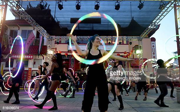 Hula Hoop enthusiasts show their skills during a flash mob with their LEDlit hoops in Chinatown Los Angeles on March 18 2016 where attendees from...