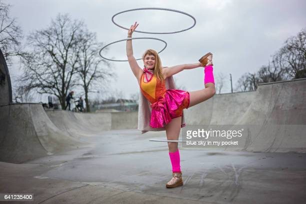 A Hula hooping girl in a bright costume dancing with 3 hoops