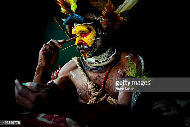 Huli Wigman waits out a rainstorm smoking and applying his traditional face paint while waiting for the rain to clear Tari Gap Papua New Guinea 17...