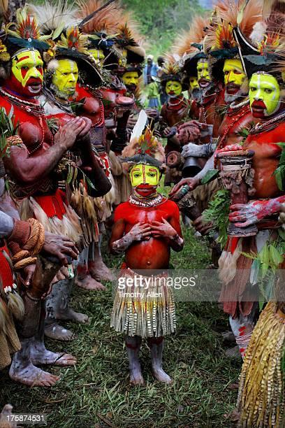 Huli wigmen and young Huli girl in tribal dress