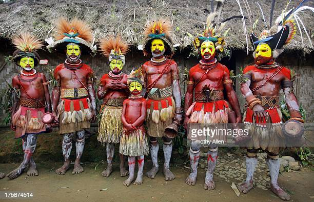 Huli Wigmen standing by thatched hut