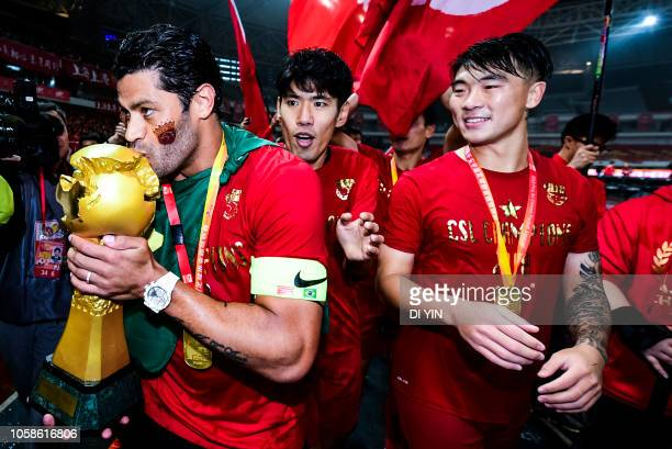 Hulk kisses of Shanghai SIPG kisses the Chinese Super League trophy after winning the Chinese Super League championship against Beijing Renhe during...
