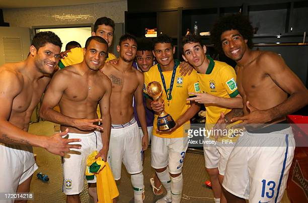 Hulk Lucas Hernanes Neymar Marcelo Thiago Silva Oscar and Dante of Brazil pose with the trophy in the dressing room at the end of the FIFA...