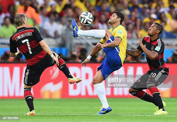 Hulk of Brazil controls the ball against Bastian Schweinsteiger and Jerome Boateng of Germany during the 2014 FIFA World Cup Brazil Semi Final match...