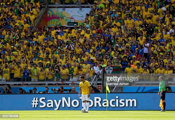 Hulk of Brazil stands in front of Brazil fans and a sign saying Say not to Racism