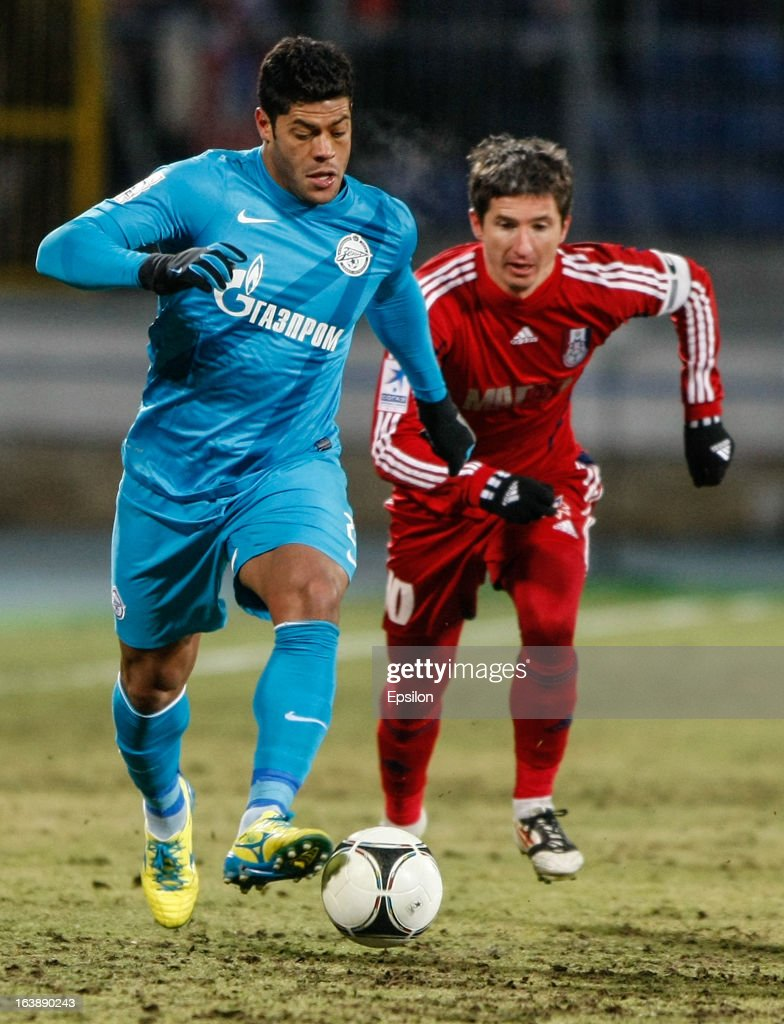 Hulk of FC Zenit St. Petersburg (L ) and Evgeni Aldonin of FC Mordovia Saransk vie for the ball during the Russian Football League Championship match between FC Zenit St. Petersburg and FC Mordovia Saransk at the Petrovsky Stadium on March 17, 2013 in St. Petersburg, Russia.