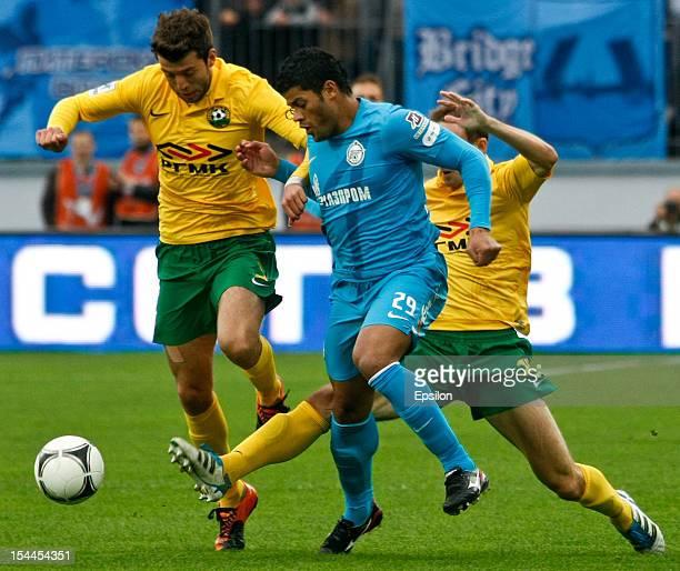 Hulk of FC Zenit St Petersburg vies for the ball with Angel Dealbert of FC Kuban Krasnodar and Aleksei Kozlov of FC Kuban Krasnodar during the...