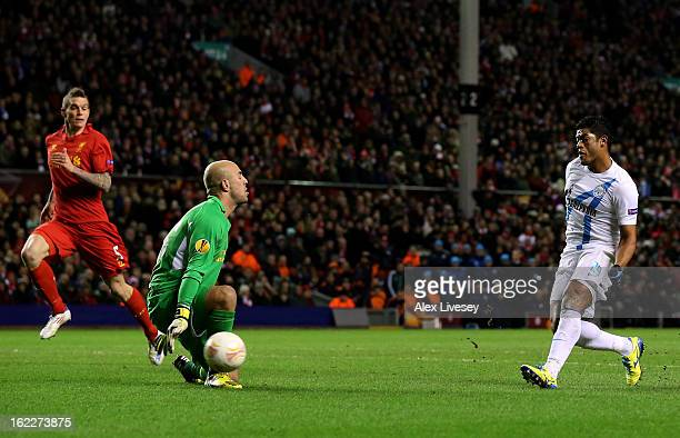 Hulk of Zenit scores the opening goal past goalkeeper Pepe Reina of Liverpool during the UEFA Europa League round of 32 second leg match between...
