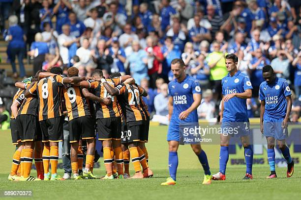 Hull City players create a huddle after the final whistle while the Leicester City players show dejection during the Premier League match between...