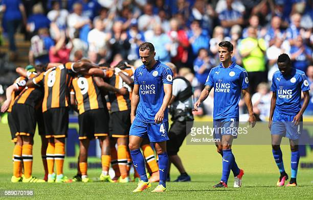 Hull City players create a huddle while Leicester City players walk off the pitch dejected after the final whistle during the Premier League match...