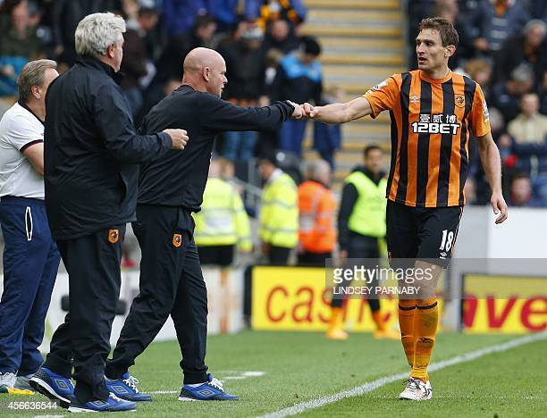 Hull City's Croatian striker Nikica Jelavic celebrates scoring their second goal with assistant manager Steve Agnew during the English Premier League...