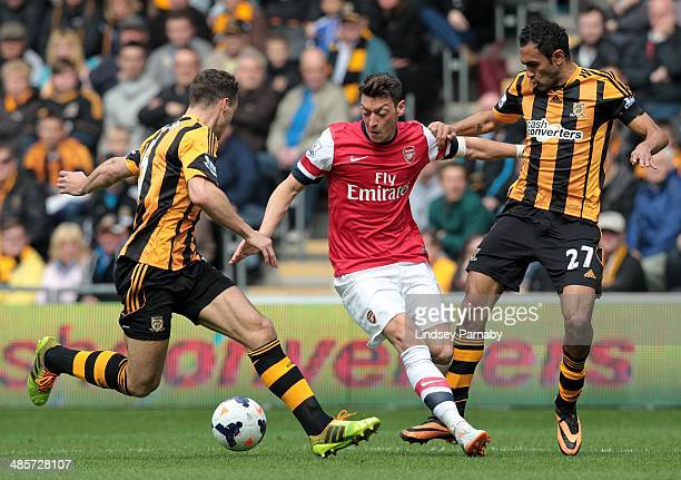 Hull City's Egyptian midfielder Ahmed Elmohamady and English defender James Chester challenge Arsenal's German midfielder Mesut Ozil during the...