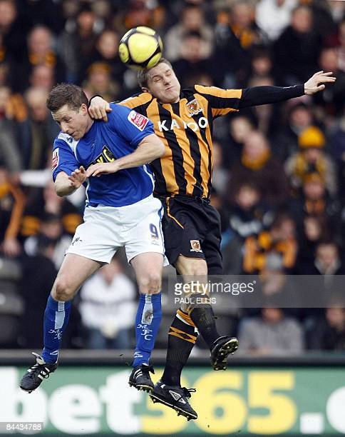 Hull City's English defender Andy Dawson jumps with Millwall's Neil Harris for the ball during their English FA Cup football match at The Kingston...