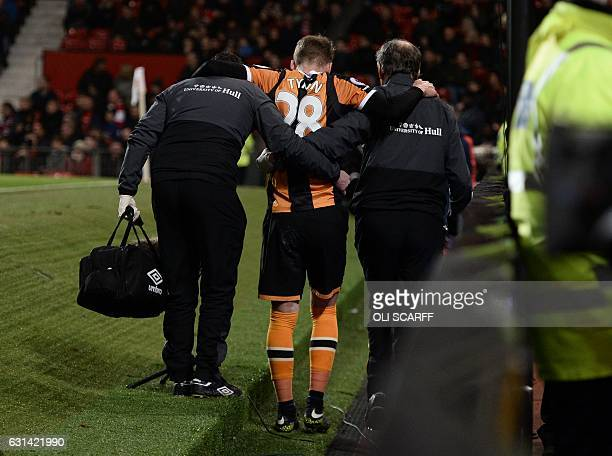 Hull City's English defender Josh Tymon is helped off the pitch injured during the EFL Cup semifinal football match between Manchester United and...