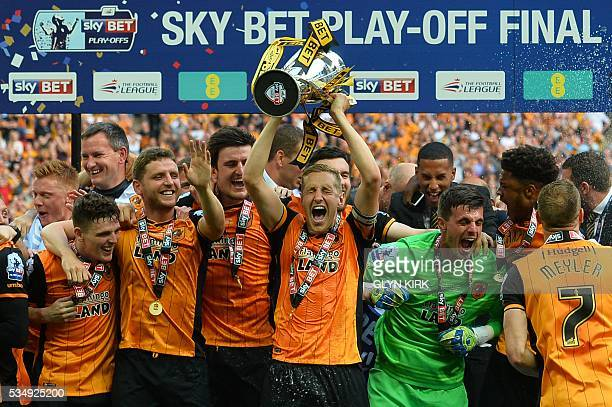 Hull City's English defender Michael Dawson lifts the trophy during the presentation after Hull City won the English Championship playoff final...