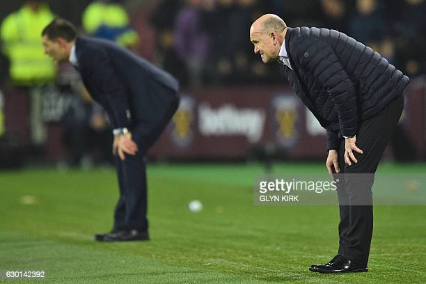 Hull City's English manager Mike Phelan and West Ham United's Croatian manager Slaven Bilic react on the touchline during the English Premier League...