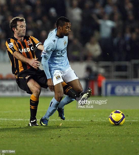 Hull City's English midfielder Ian Ashbee tackles Manchester City's Brazilian forward Robinho during their English Premier League football match at...