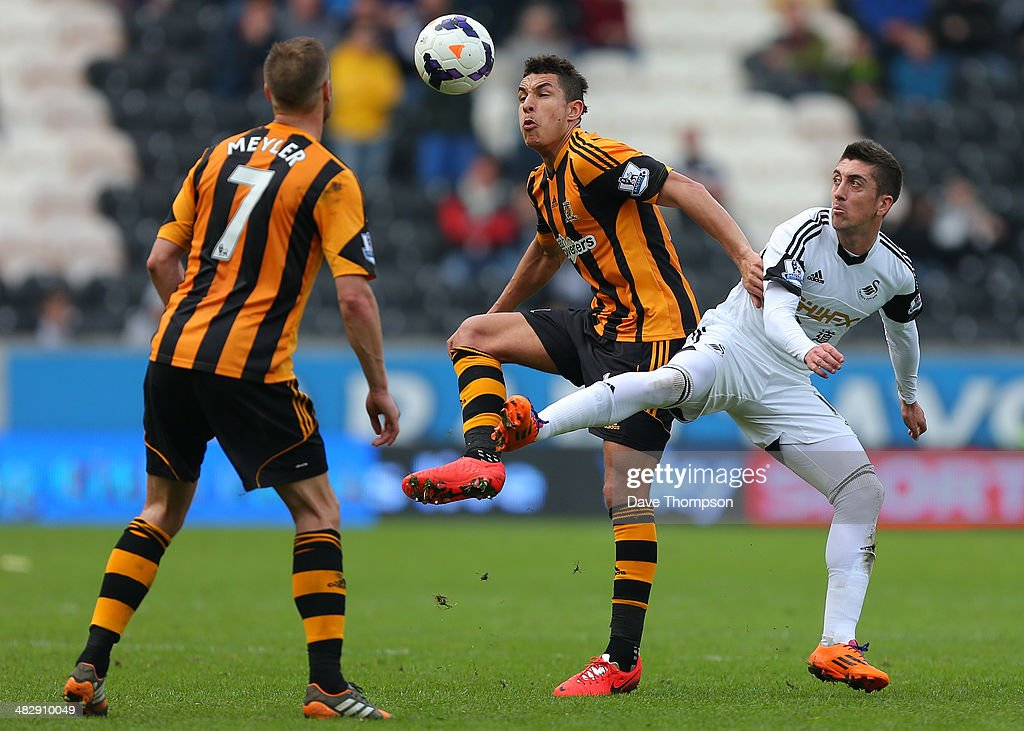 Hull City's Jake Livermore is challenged by Swansea City's Pablo Hernandez during the Barclays Premier League match between Hull City and Swansea City at KC Stadium on April 5, 2014 in Hull, England.