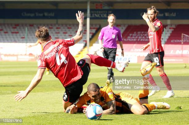 Hull City's Mallik Wilks goes down under the challenge from Lincoln City's Lewis Montsma during the Sky Bet League One match between Lincoln City and...