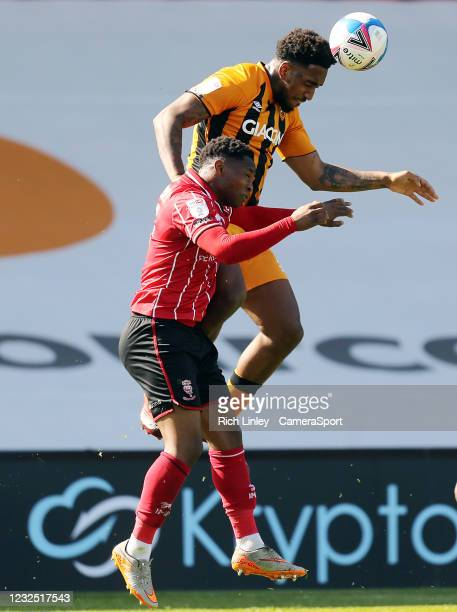 Hull City's Mallik Wilks wins a header despite the attentions of Lincoln City's Tayo Edun during the Sky Bet League One match between Lincoln City...