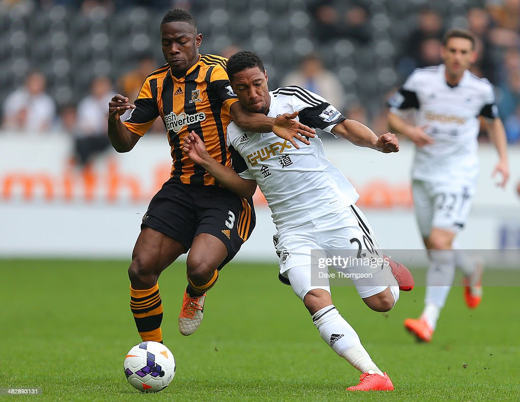 Hull City's Maynor Figueroa and Swansea City's Jonathan de Guzman compete or the ball during the Barclays Premier League match between Hull City and Swansea City at KC Stadium on April 5, 2014 in Hull, England.