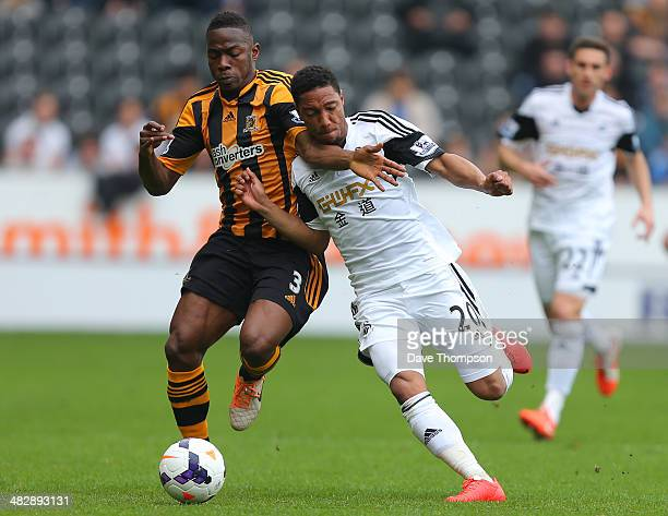 Hull City's Maynor Figueroa and Swansea City's Jonathan de Guzman compete or the ball during the Barclays Premier League match between Hull City and...