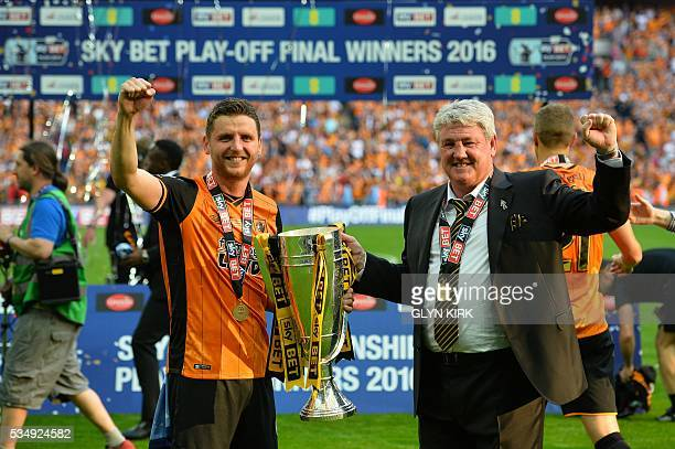 Hull City's Northern Irish defender Alex Bruce and Hull City's English manager Steve Bruce celebrate with the trophy after Hull City won the English...