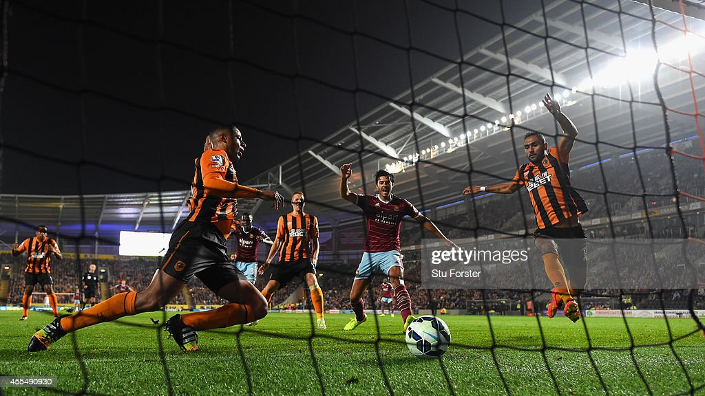 Hull defender Curtis Davies (l) diverts the ball into his own net as West Ham defender James Tomkins (c) celebrates the second West Ham goal during the Barclays Premier League match between Hull City and West Ham United at KC Stadium on September 15, 2014 in Hull, England.