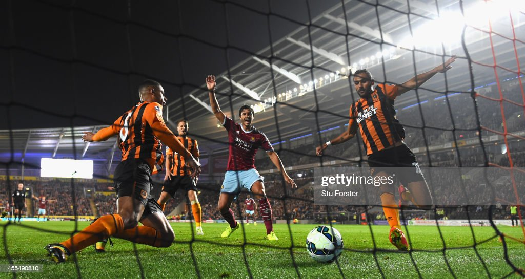 Hull defender Curtis Davies (l) ldiverts the ball into his own net as West Ham defender James Tomkins (c) celebrates the second West Ham goal during the Barclays Premier League match between Hull City and West Ham United at KC Stadium on September 15, 2014 in Hull, England.