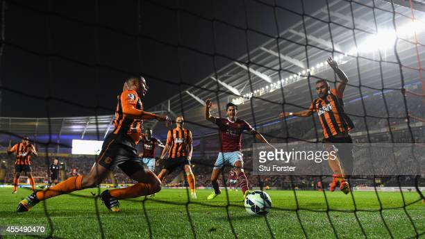 Hull defenders look on as West Ham defender James Tomkins celebrates the second West Ham goal during the Barclays Premier League match between Hull...