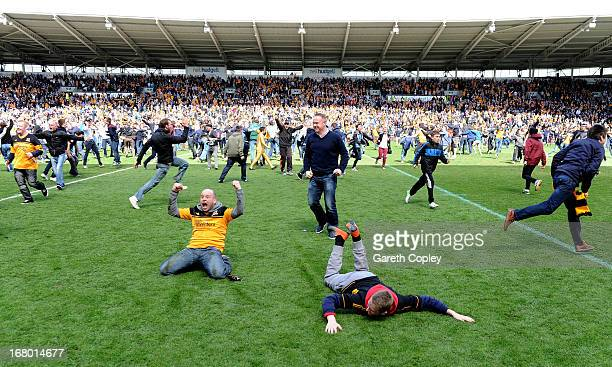 Hull fans fans run onto the pitch to celebrate their team's promotion to the Premier League during the npower Championship match between Hull City...