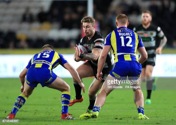 Hull FC's Jansin Turgut is tackled by Warrington Wolves' Brad Dwyer and Jack Hughes during the Betfred Super League match at the KCOM Stadium Hull