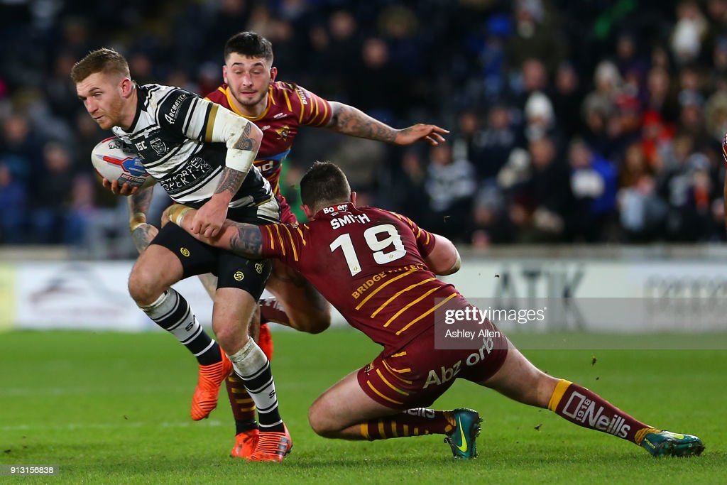 Hull FC's Marc Sneyd (L) is tackled by Daniel Smith (R) and Oliver Roberts (C) of Huddersfield Giants during the BetFred Super League match between Hull FC and Huddersfield Giants at KCOM Stadium on Thursday, February 1, 2018 in Hull, England.