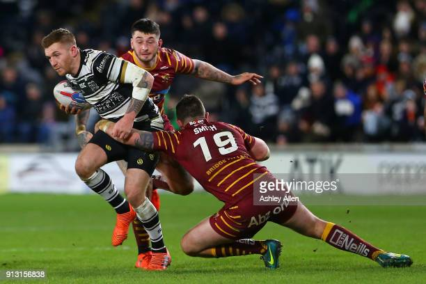 Hull FC's Marc Sneyd is tackled by Daniel Smith and Oliver Roberts of Huddersfield Giants during the BetFred Super League match between Hull FC and...