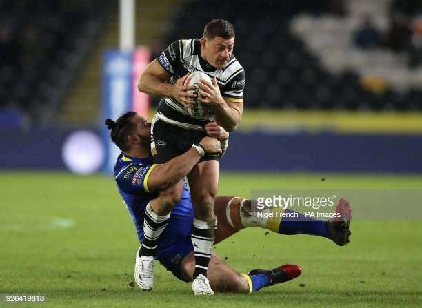 Hull FC's Mark Minichiello is tackled by Warrington Wolves Ben MurdochMasila during the Betfred Super League match at the KCOM Stadium Hull