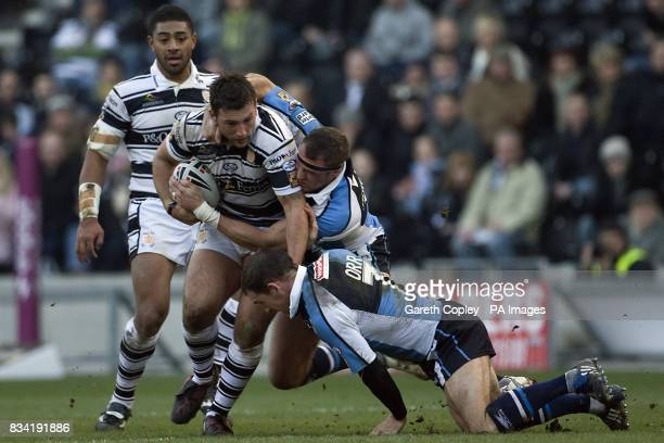 Hull FC's Tommy Lee is tackled by Harlequins' Rob Purdham and Danny Orr