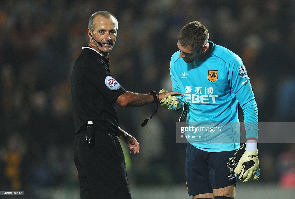 Hull goalkeeper Allan McGregor checks the watch of referee Martin Atkinson at the end of the Barclays Premier League match between Hull City and West Ham United at KC Stadium on September 15, 2014 in Hull, England.