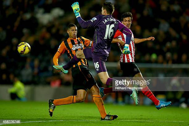 Hull goalkeeper Eldin Jakupovic charges out to clear the ball past Curtis Davies of Hull and Jack Cork of Southampton during the Barclays Premier...