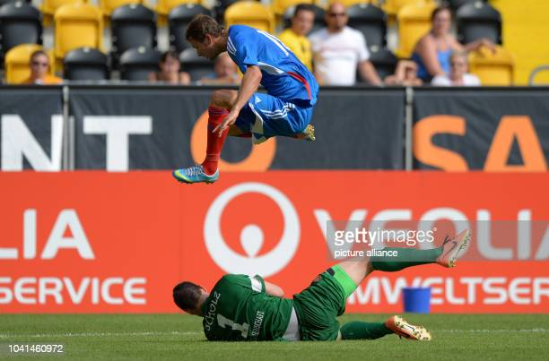 Hull's Nick Proschwitz jumps over Dresden's goalkeeper Markus Scholz during the friendly match between SGDynamoDresden and Hull City AFC at...