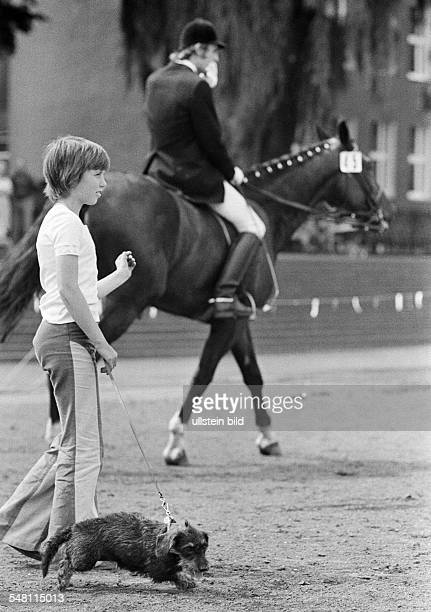 human and animal young boy walks a dog on a lead in the background a dressage horse with horseman aged 10 to 13 years Ruhr area North RhineWestphalia