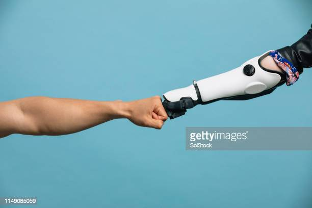 a human and robotic arm making a fist bump - human arm stock pictures, royalty-free photos & images