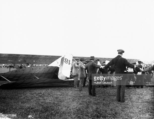 Human cordon prevents onlookers from interferring with the work of the medical services as they attempt to rescue the English aviator, Charles...