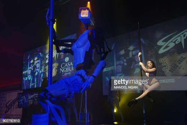 A human dancer performs next to a stripper robot at the Sapphire Gentlemen's Club on the sidelines of CES 2018 in Las Vegas on January 8 2018 / AFP...