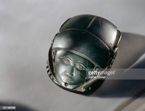 A human faced heart scarab which was placed on the deceaseds heart during burial rites The original Middle Kingdom text on the base has been erased...
